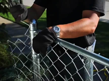 A worker is repairing chain link fencing.