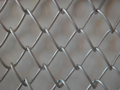 A piece of galvanized diamond wire mesh on the gray background.