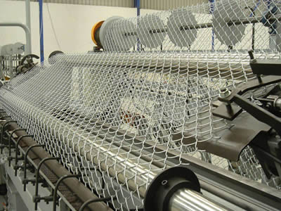 Chain link fence is produced by a fully automatic machine.